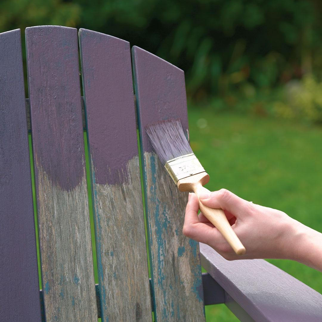 Nærbilde av en stol som blir malt lilla i hagen
