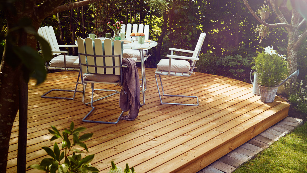 en flott uteplass med beiset terrassegulv og 4 stoler med bord