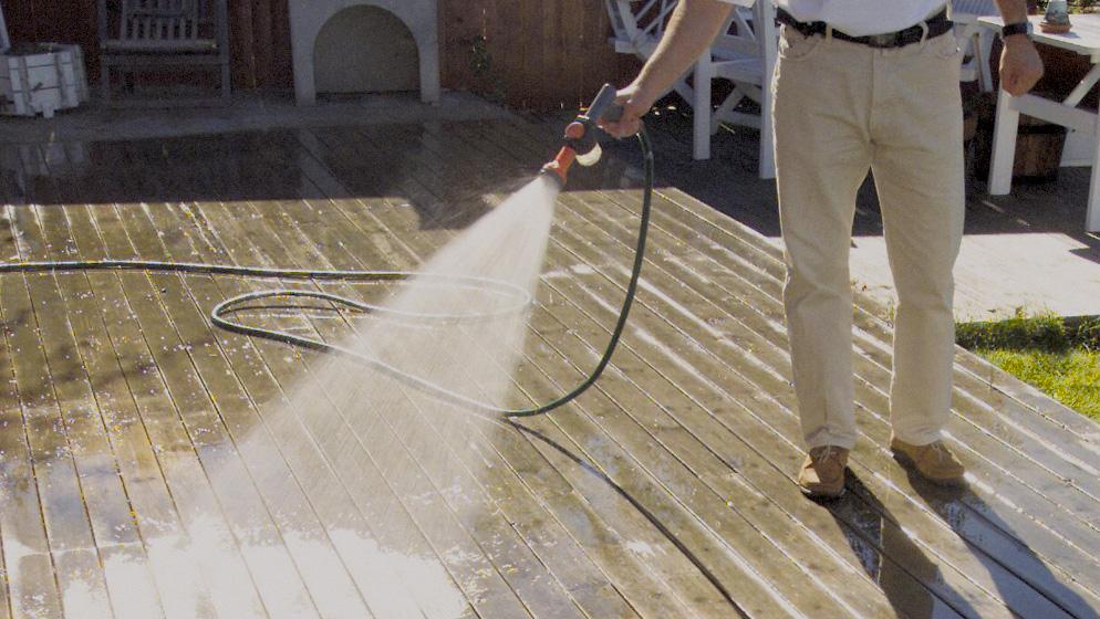 Mann som spyler terrassen ren med hageslangen