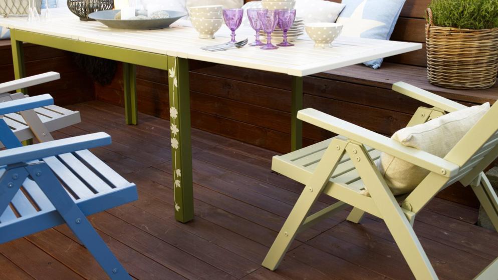 Stoler i grønt og blått foran et bord på terrassen