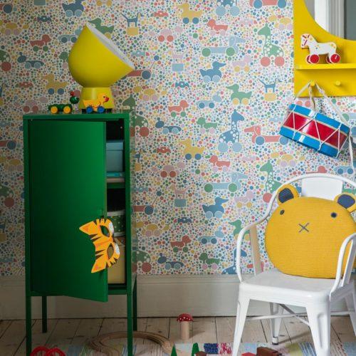 Et fargerikt barnerom med grønt skap og hvit stol med en gul pute